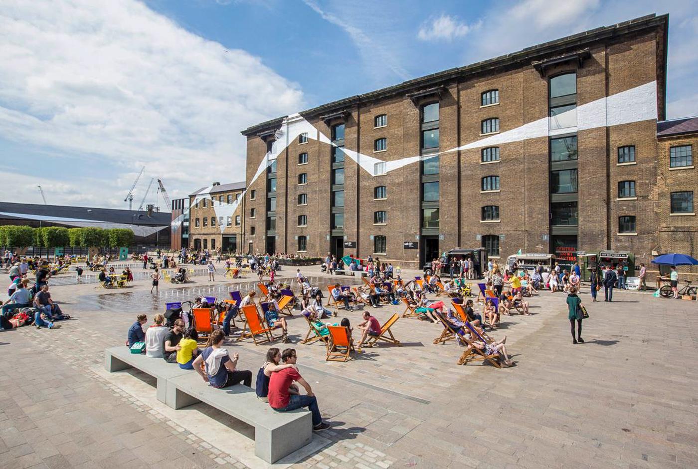 Grand terre-plein ensoleillé de Granary Square à Londres. Gens dans des chaises longues colorées. Immeuble en briques avec une bande blanche peinte