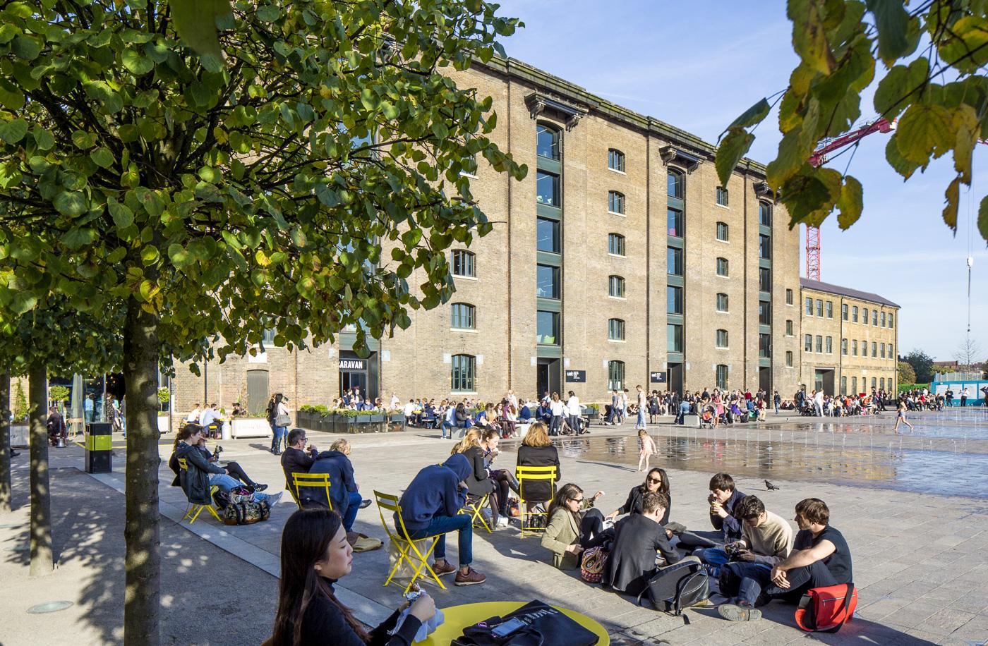 Gens assis sous les arbres, devant les fontaines et l'immeuble en brique de Granary Square à Londres