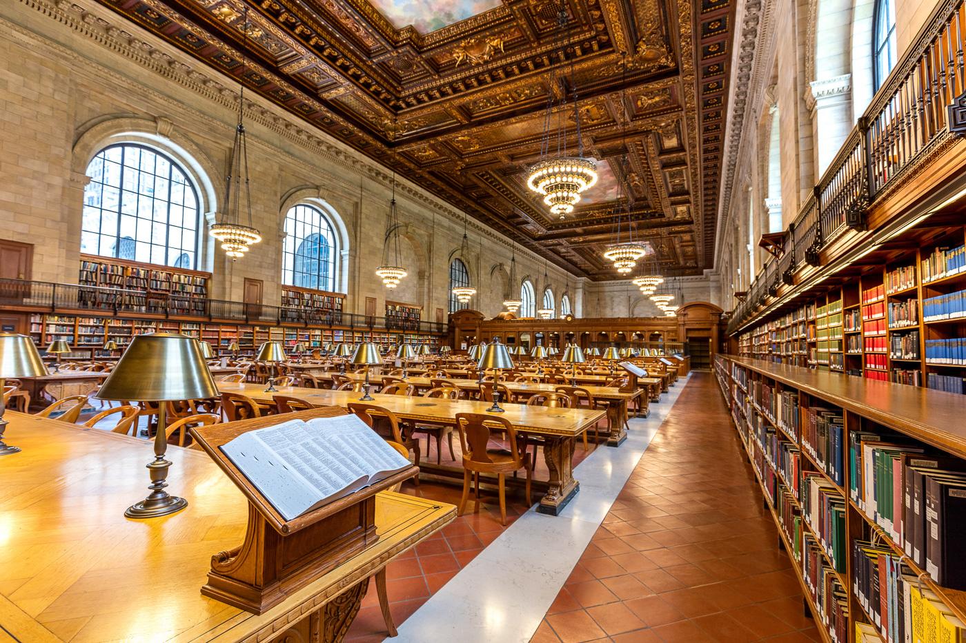 Vue d'ensemble des bibliothèques, lustres et tables de travail de la luxueuse New York Public Libary avec un livre posé sur un pupitre au premier plan