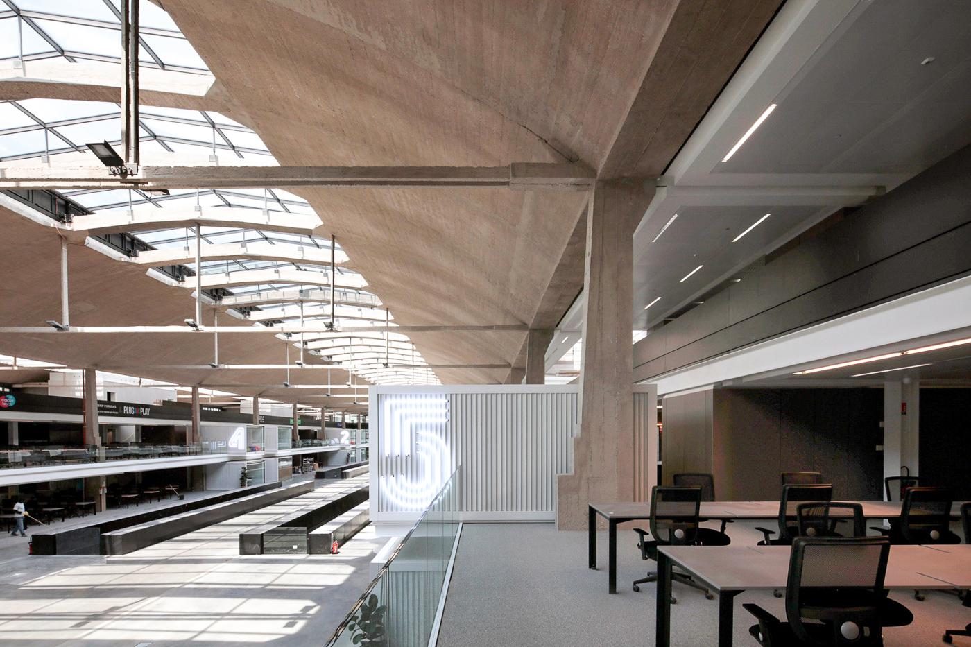 Plafond en béton avec verrières et bureaux avec ordinateurs à l'étage supérieur de Station F