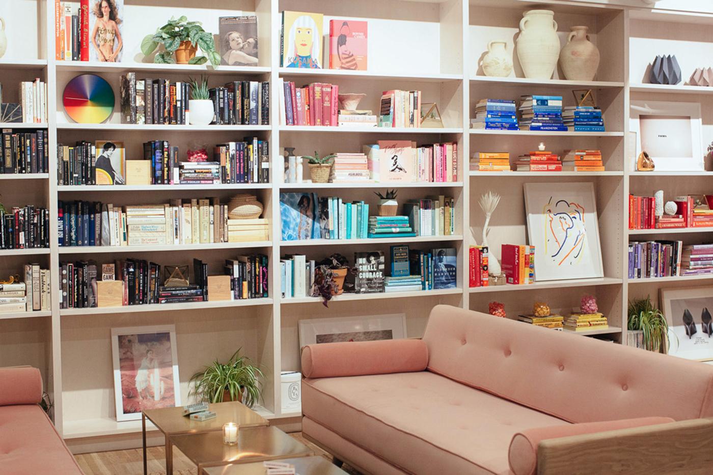 Canapé rose vintage et bibliothèque remplie de livres et poteries à The Wing, espace de coworking à New York