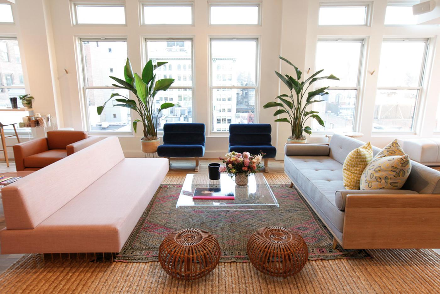 Salon d'esprit 60's avec deux canapés et des plantes devant une baie vitrée, à The Wing, espace de coworking à New York