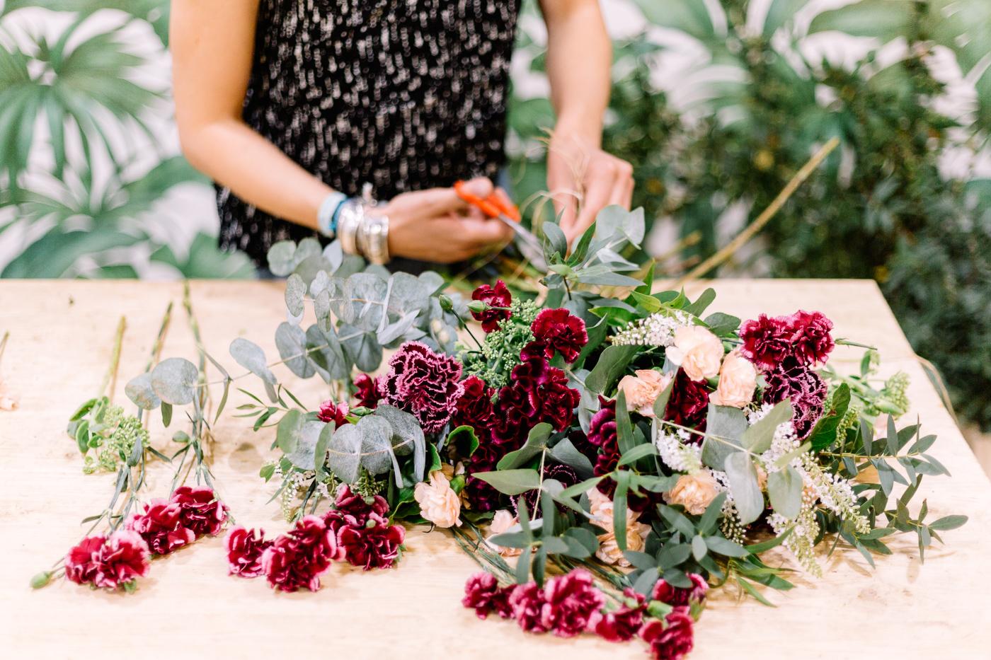 Des mains de femmes coupant des feuilles pour composer un bouquet de fleurs roses