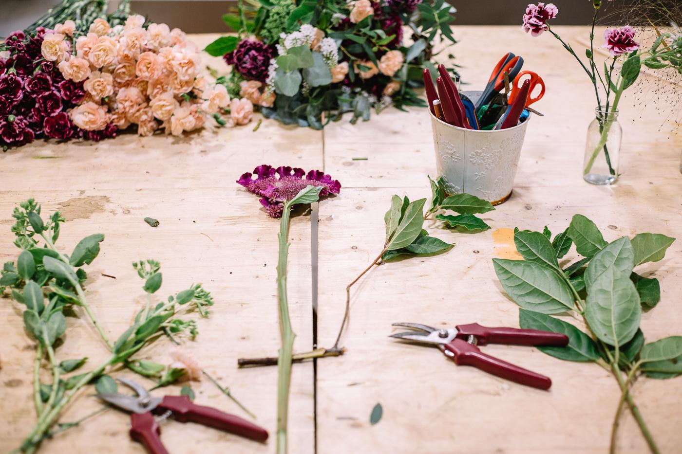 Une table de l'atelier de fleuriste de Pampa, avec des fleurs, des sécateurs et un pot à crayon