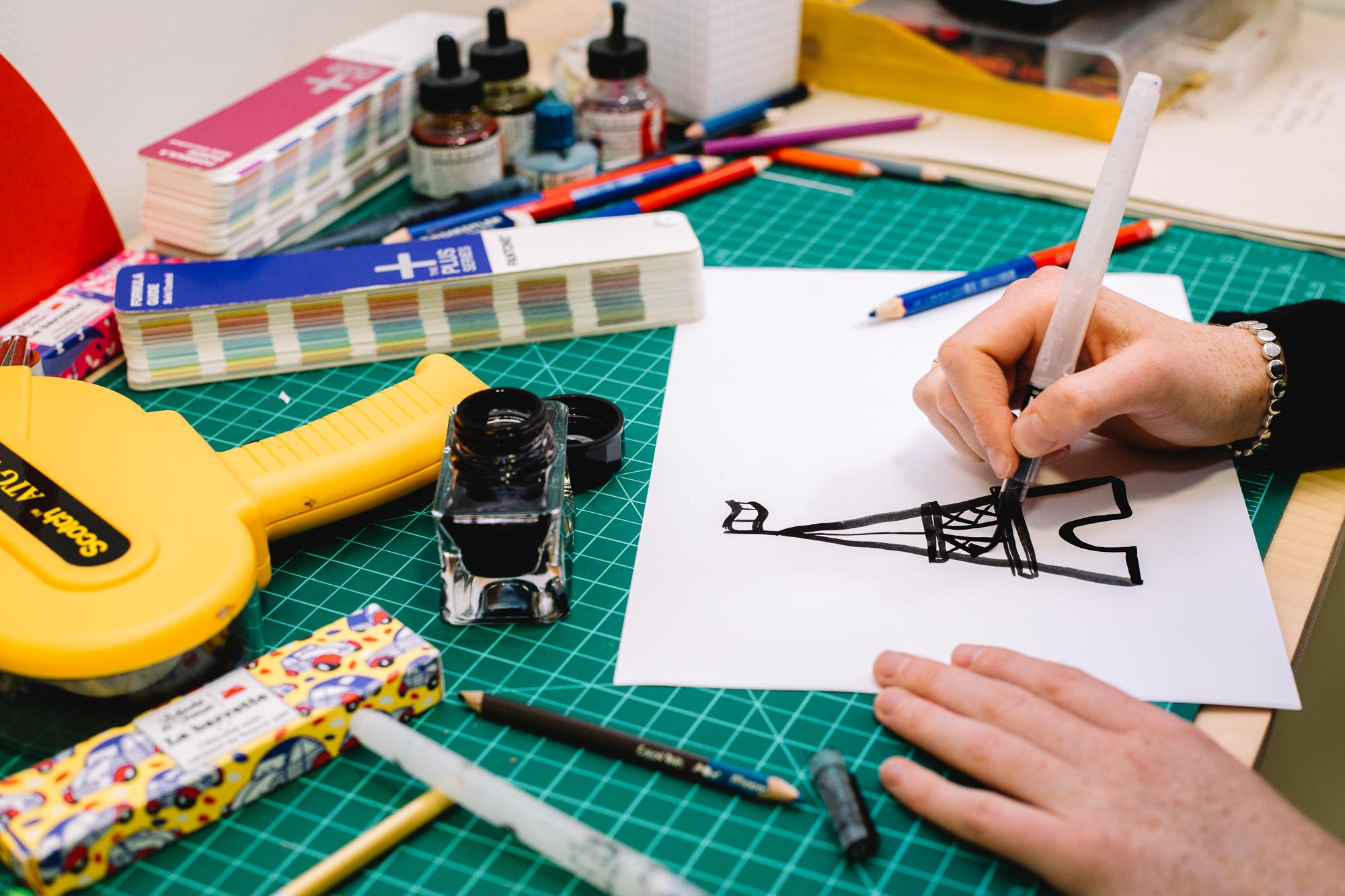Un bureau de dessinateur avec une main dessinant une Tour Eiffel à l'encre noire, un encrier, des outils de dessin et une barre de chocolat Le Chocolat des Français