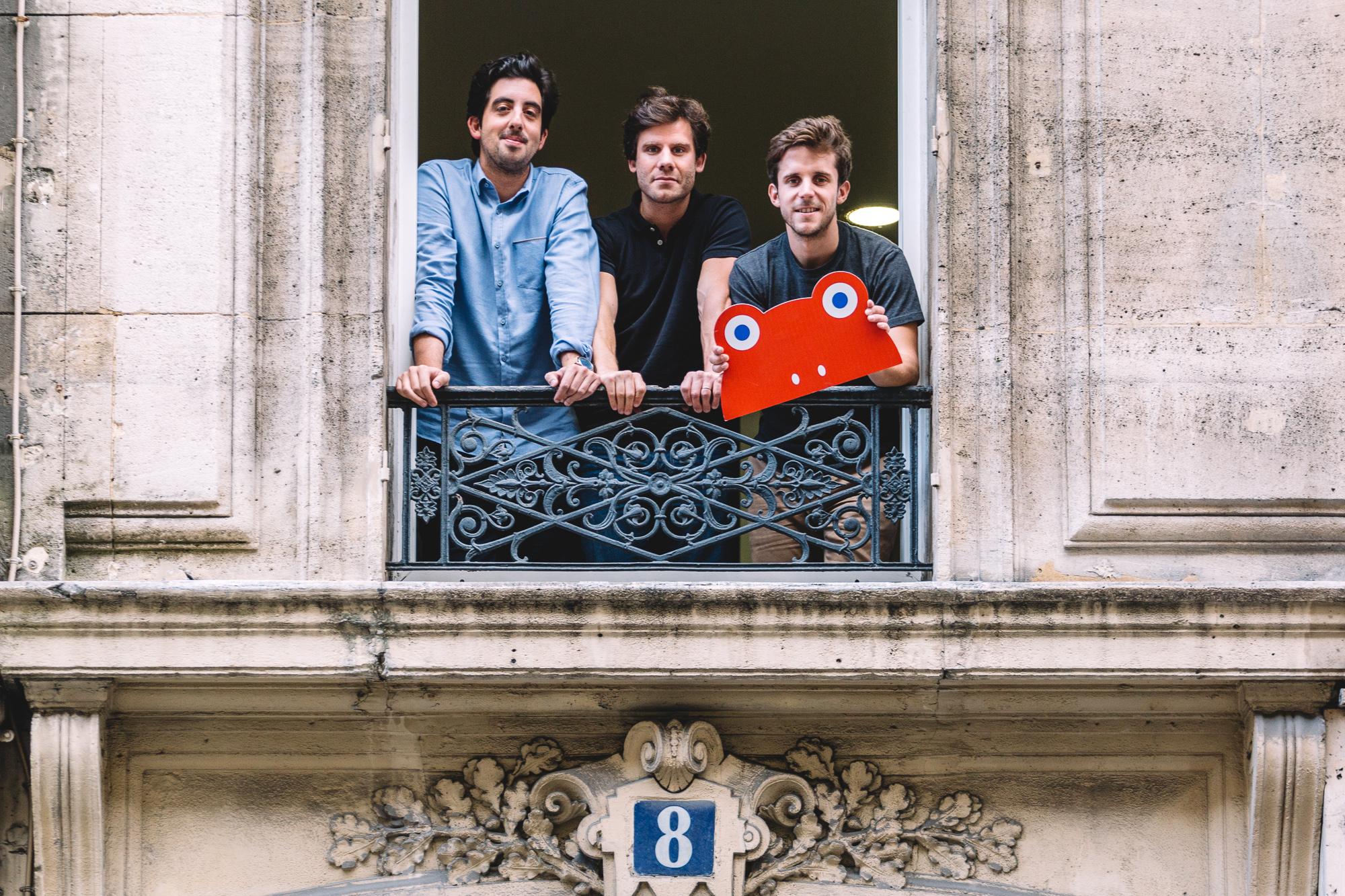 Les trois fondateurs du Chocolat des Français, à une fenêtre d'immeuble parisien avec leur logo grenouille