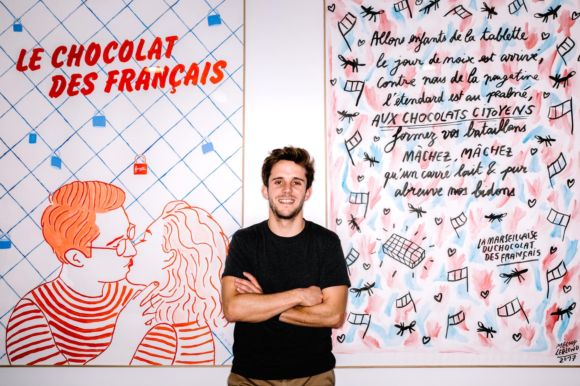 Vincent Muraire du Chocolat des Français devant un grand poster Le Chocolat des Français et un autre qui parodie Les paroles de la Marseillaise en parlant de chocolat
