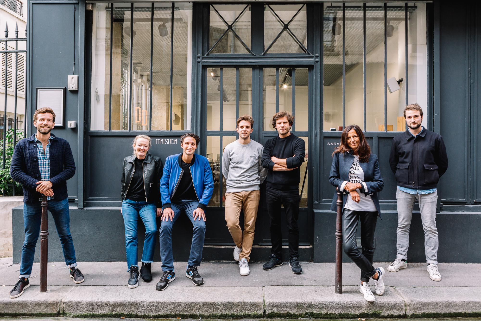 Une dizaine d'hommes et femmes posant devant un atelier industriel parisien