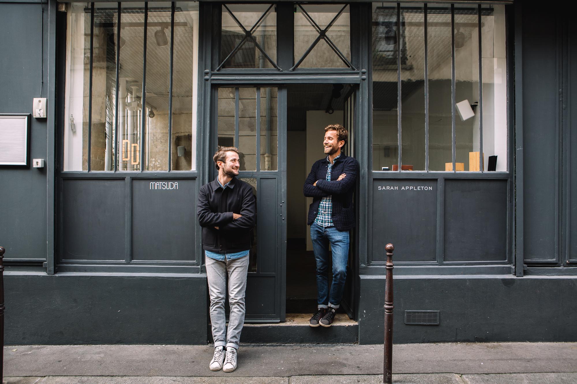 Deux jeunes hommes se sourient devant un ancien atelier parisien