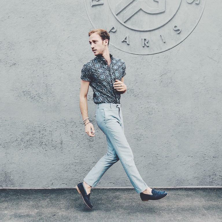 Romain Costa, architecte et blogueur mode marchant devant un mur marqué Paris