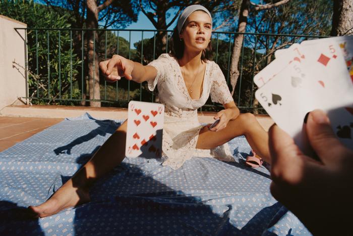 Campagne de la marque Miræ - une fille vêtue d'une robe blanche et d'un foulard dans les cheveux assise sur un matelas sur une terrasse ensoleillée tend une carte à jouer vers une main qui tient aussi des cartes