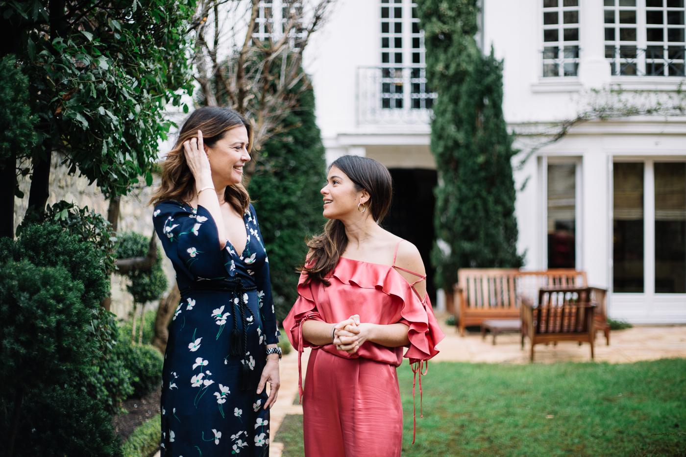 Camille Jarmon se regardent en souriant, vêtues de vêtements de soirées Miræ, avec leur jardin et la maison familiale en arrière-plan