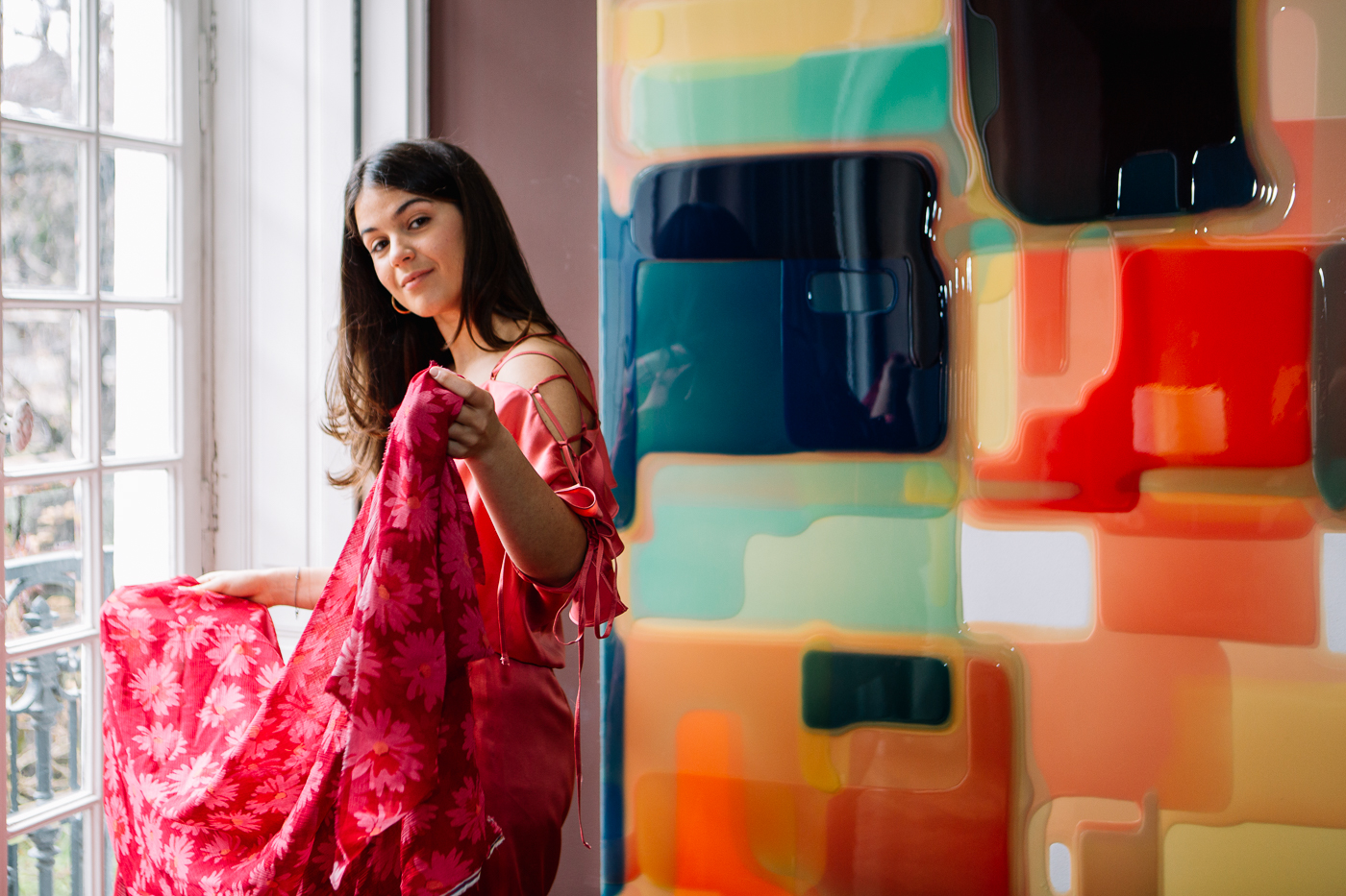 Camille Jarmon habillée d'une combinaison en soie rose Miræ se tient devant une fenêtre et montre une étoffe rose imprimée de fleurs avec à côté d'elle un tableau de Peter Zimmerman