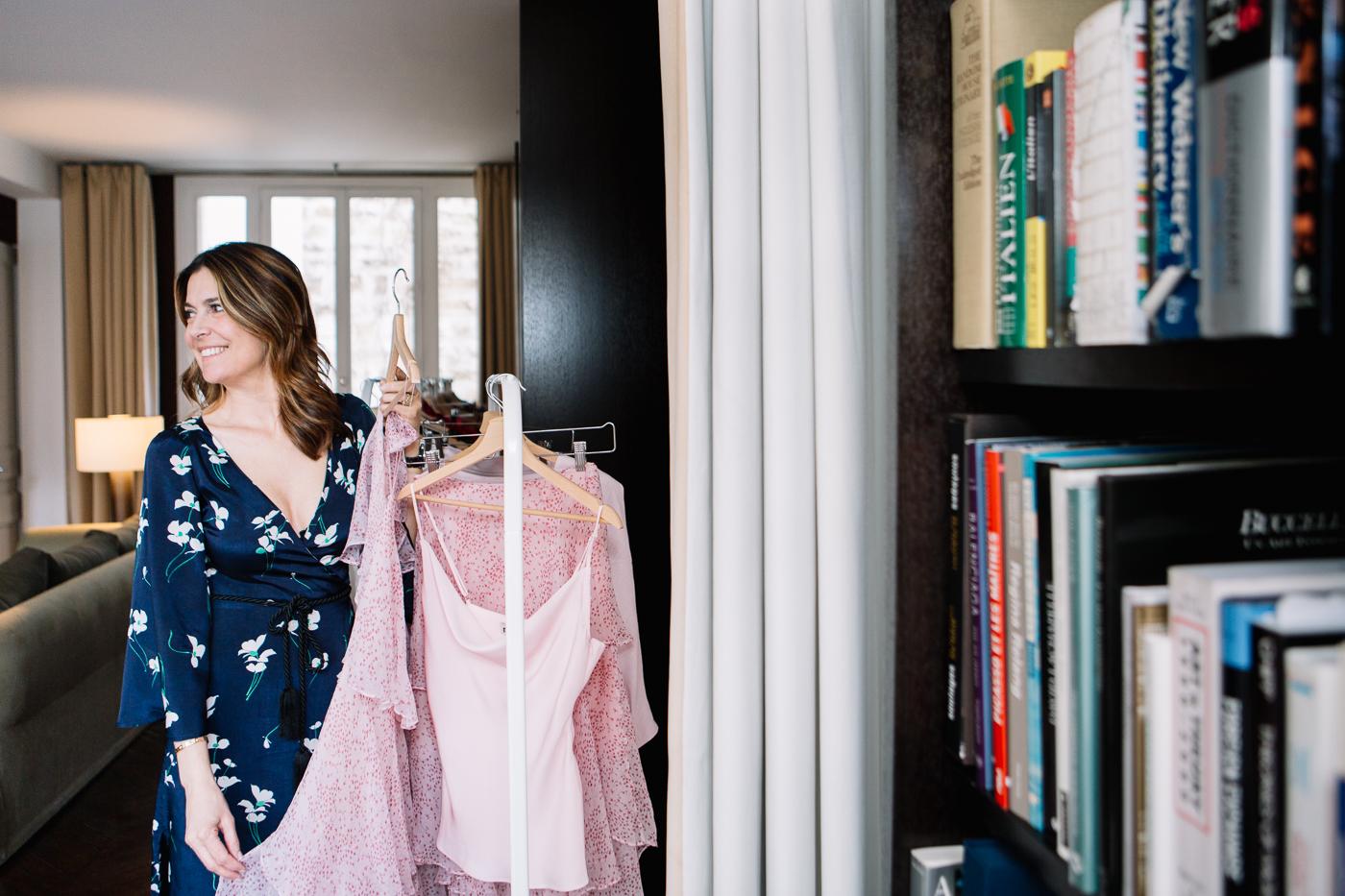 Tara Jarmon dans son salon, vêtue d'une robe kimono bleue imprimée issue de sa nouvelle marque Miræ, se tient devant un rail de vêtements et présente une robe rose vaporeuse