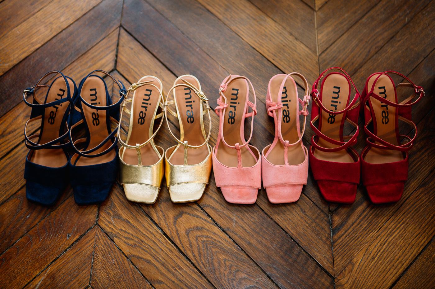 Quatre paires de sandales à talons de la marque Miræ roses, bleues et dorées sur un parquet