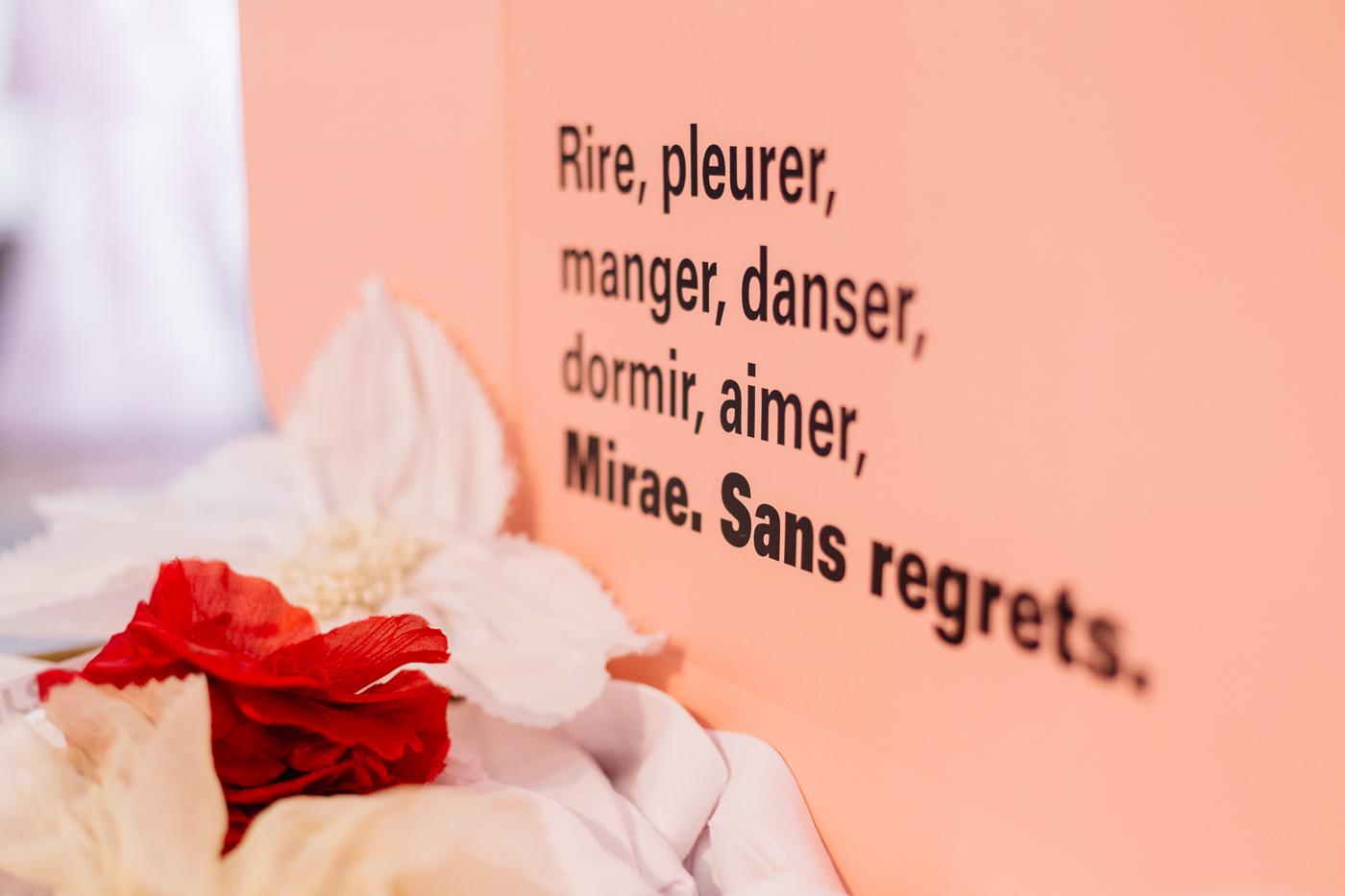 """Derrière des fleurs rouges et blanches floutées, une pancarte rose de la marque Miræ, marquée Rire, pleurer, manger, danser, dormir aimer et en gras """"Miræ sans regrets"""