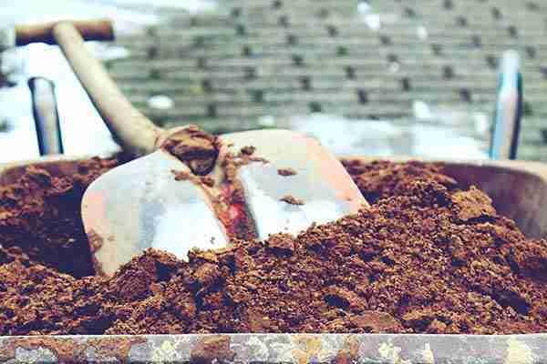 Acera con una cubeta llena de arena y una pala