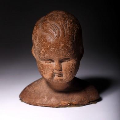 Cap de copil, fragment de statuetă din teracotă, folosită ca ofrandă, epocă romană, sec. I î.e.n. - sec. I e.n., provine din colecția dr. Horia Slobozianu
