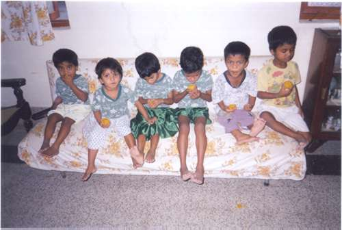 Orphans eating Ladoo
