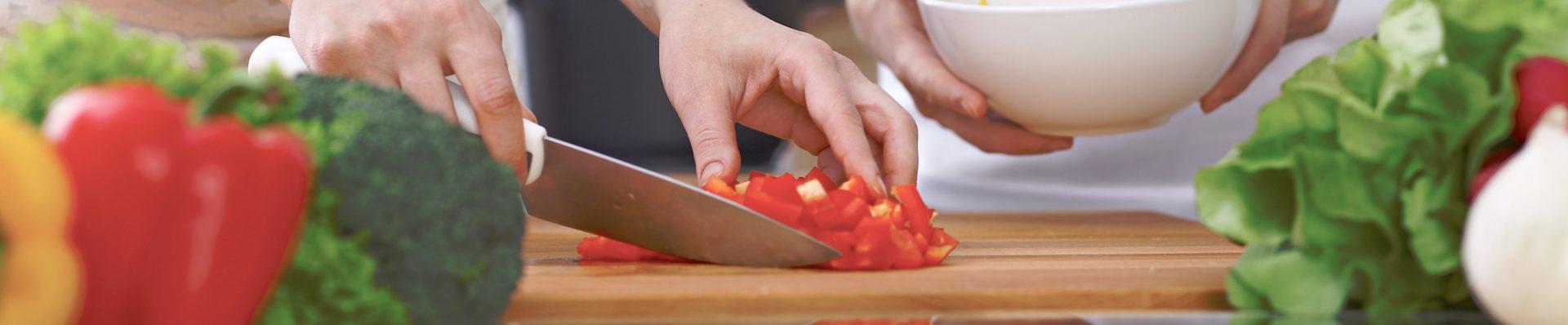 Gros plan de quatre mains en cuisine. S'amuser en préparant une salade fraîche. Végétarien, repas sain