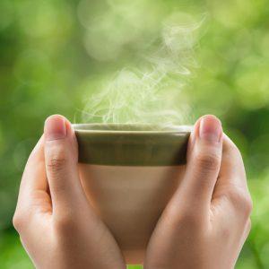 Femme, mains, tenue, thé, tasse, vert, bokeh, fond.