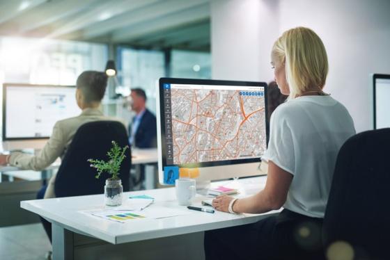 Kvinne sitter ved kontorpult og ser på en dataskjerm, som viser et kart.