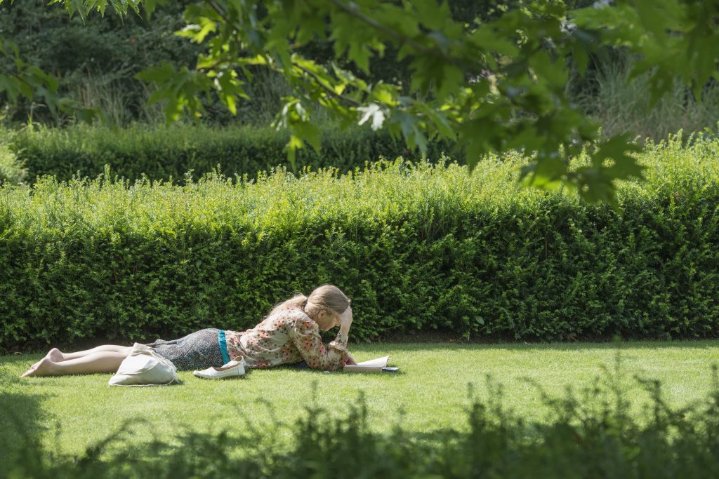 Lady lying on the grass reading a book in the summer.