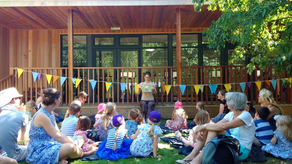 The Librarian reading to a large group of children and their guardians on the grass.