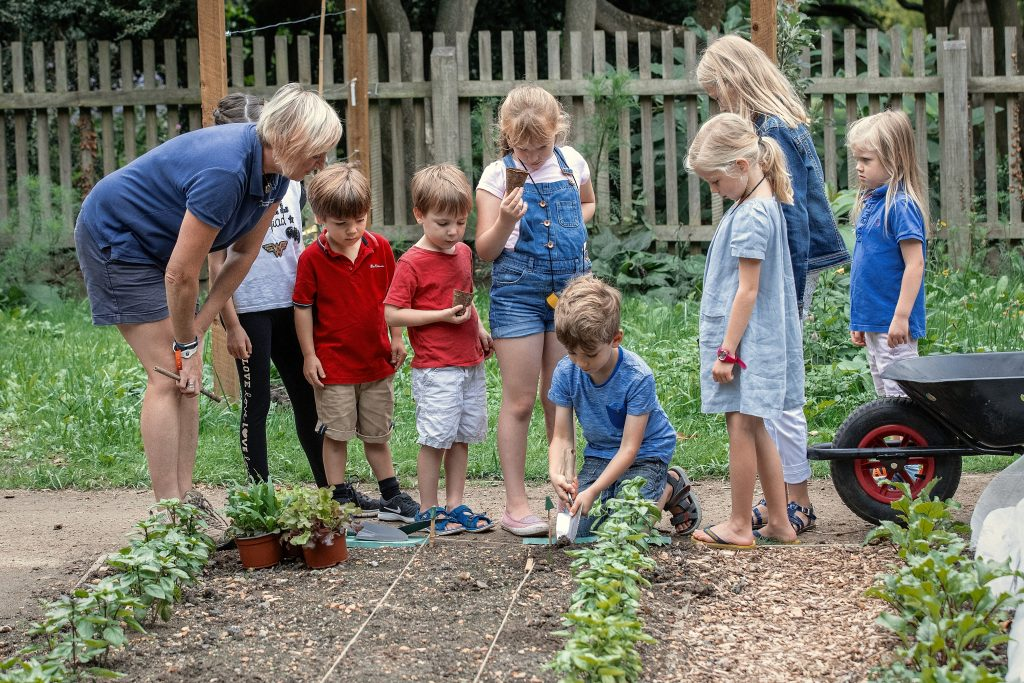 Eight children and a member of the horticulture team in the Schools' Garden.
