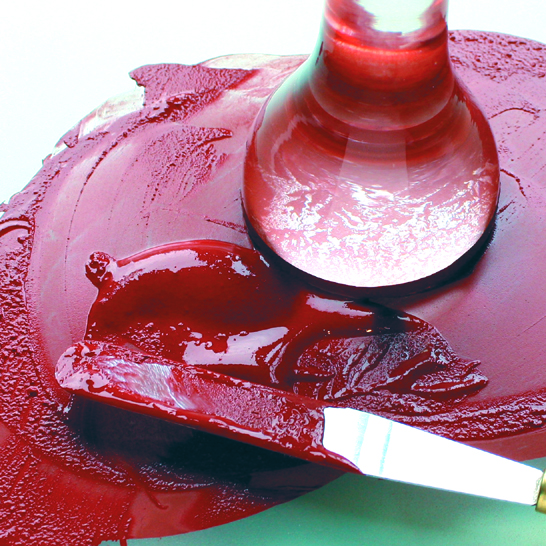 Glass pestle and metal palette knife grinding plant material to make red organic paint