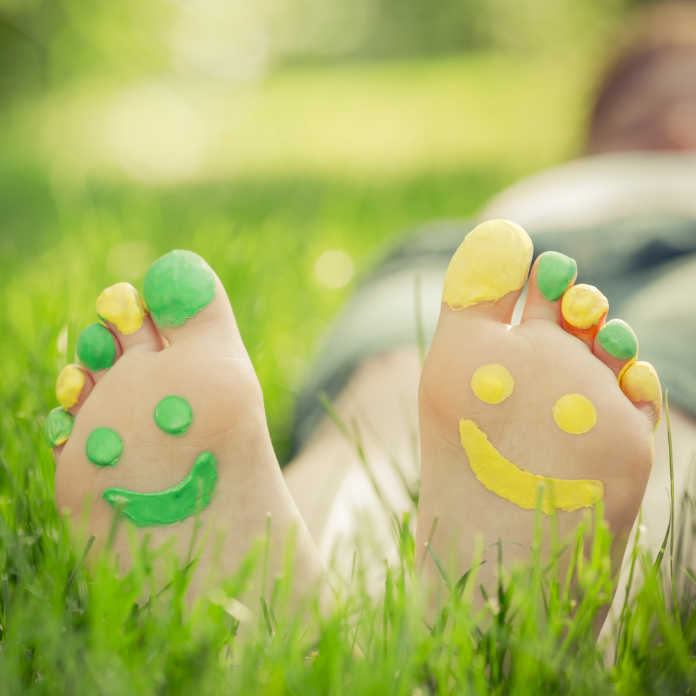 Soles of childrens feet with green and yellow painted faces