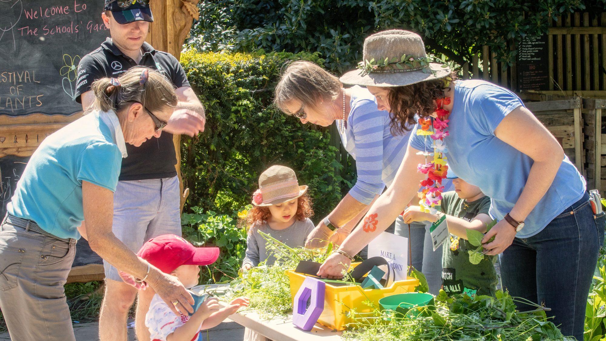 Volunteers in the schools' Garden, showing children plant material.