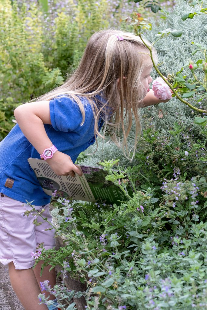 A young person smelling a rose in the Scented Garden.