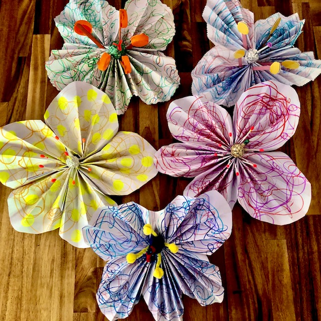 five large flowers made out of paper