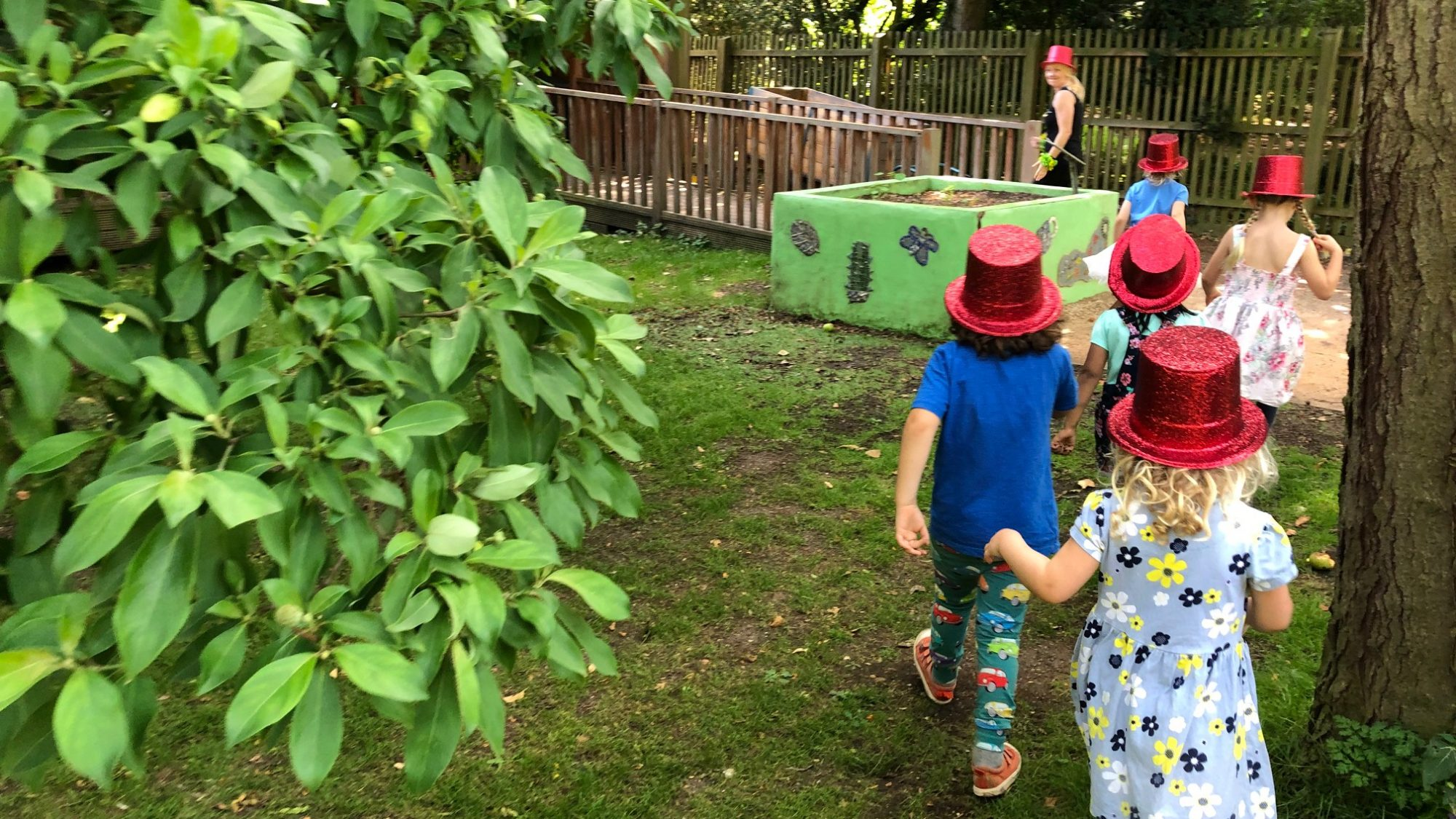 Image of children at the Botanic Garden wearing glittery red top hats
