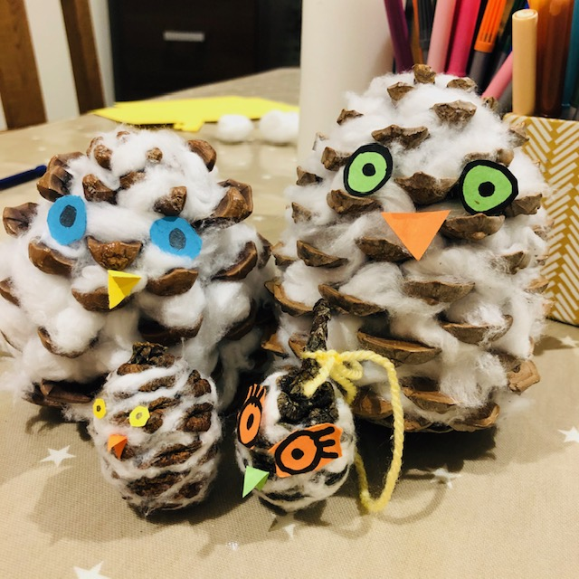 Four fluffy owls made out of pinecones and cotton wool.