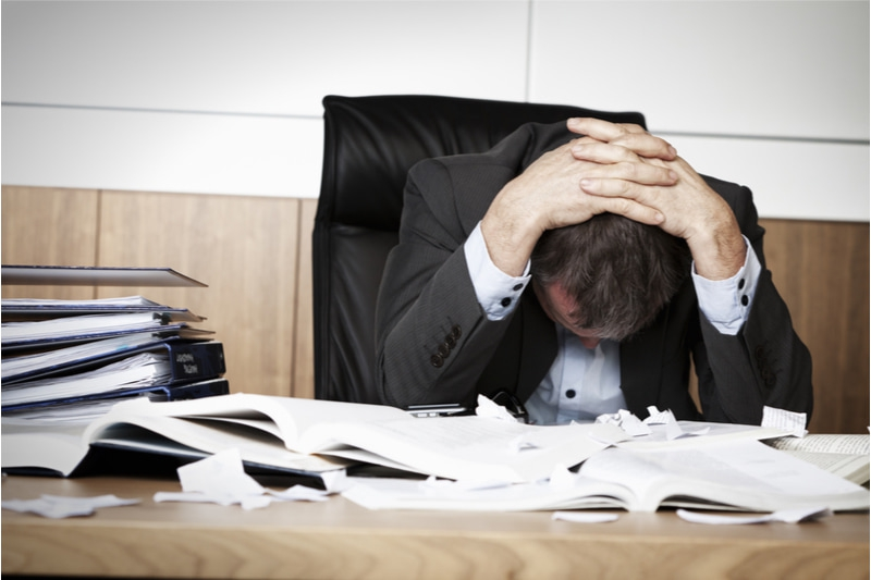 stressed employee with head on desk