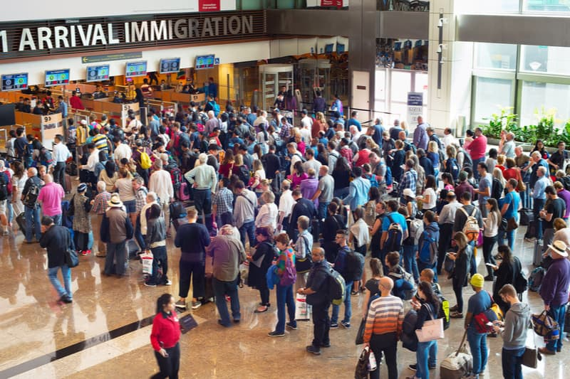 crowds of people at airport immigration gate