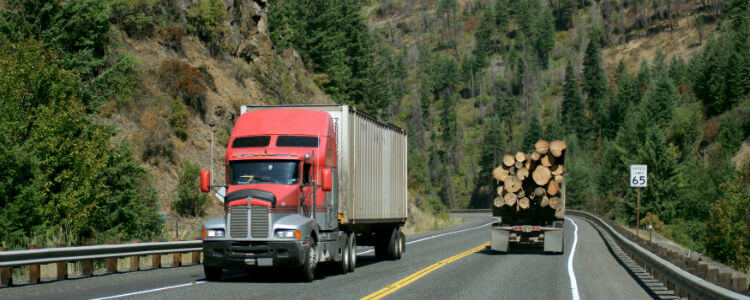 Trucks using Omnitracs and transporting logs along a road