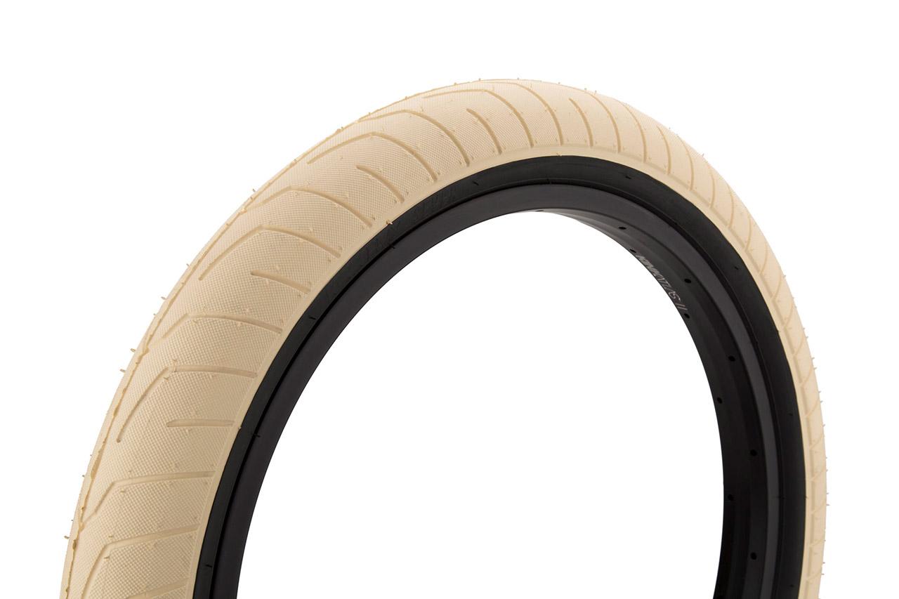 Niedriges Profil für viel Grip und wenig Rollwiderstand, 2,4'' breit und eine besondere Gummimischung für weichere Landungen: Dürfen wir vorstellen? Der Sever Tire von Kink BMX in creme mit schwarzen Seitenwänden …
