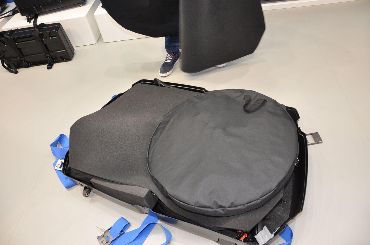 Über dem Rad wird eine Schaumstoffmatte ausgelegt, die beide Laufräder in Laufradtaschen trägt.