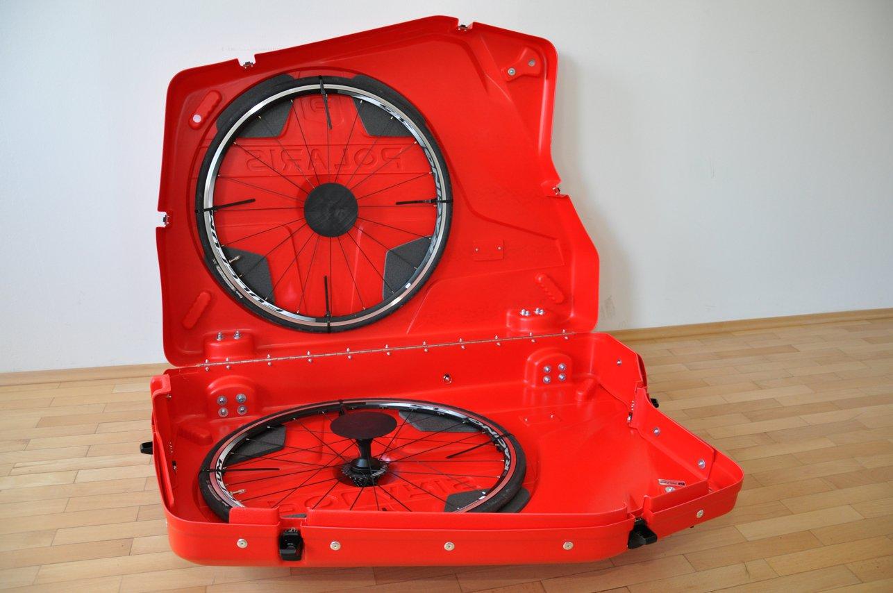 Die beiden Laufräder werden mit vier wiederverschließbaren Kabelbindern fixiert und liegen auf Schaumstoff auf. Eine Schutzkappe schützt den Rahmen vor einem Durchschlag der Nabe.