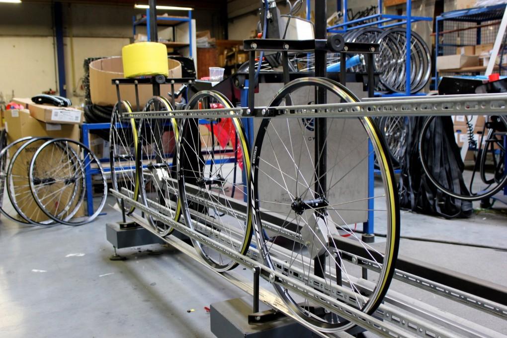 Die Laufräder werden von einer Maschine montiert und zwei weitere richten das Rad aus.