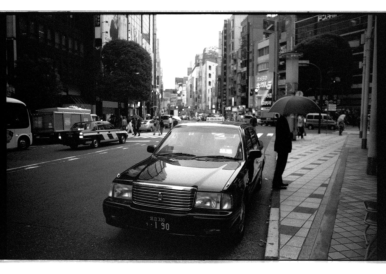 Taxi und Mann mit Regenschirm in Downtown Tokyo.