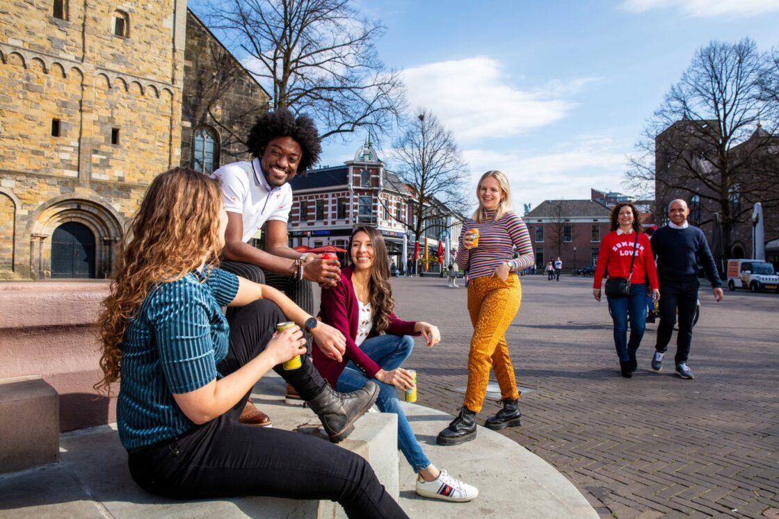 Een groep mensen geniet van de zon midden op de Oude Markt in Enschede.