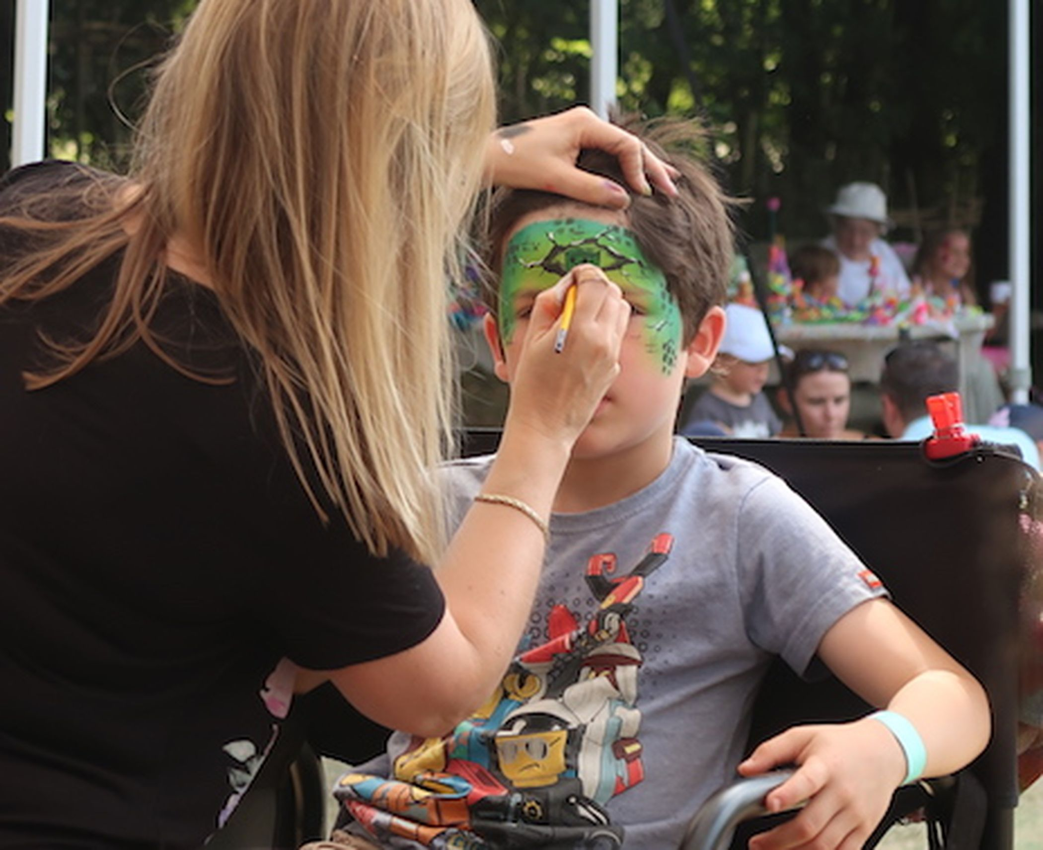 Boy getting his face painted at the Woodland Fairy Fair