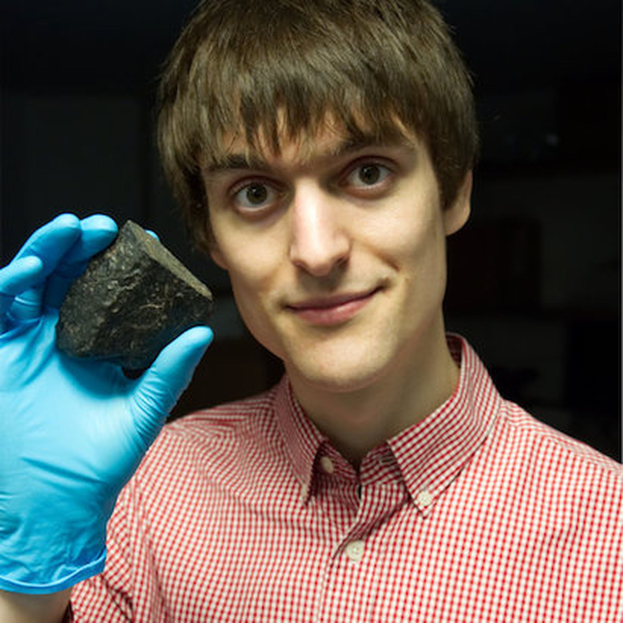 Space scientist Timothy Gregory holding a meteorite