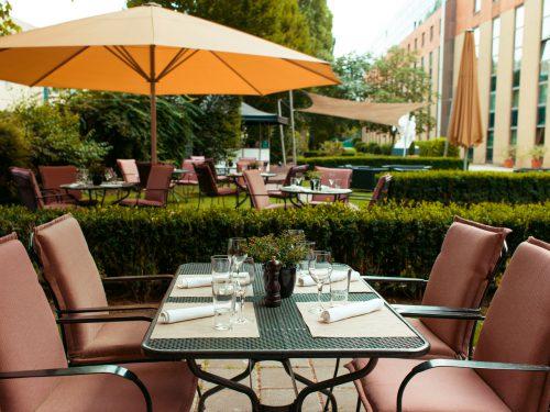 Vier Stühle rund um einen gedeckten Tisch im Garten des Imperial Riding School Vienna Hotel