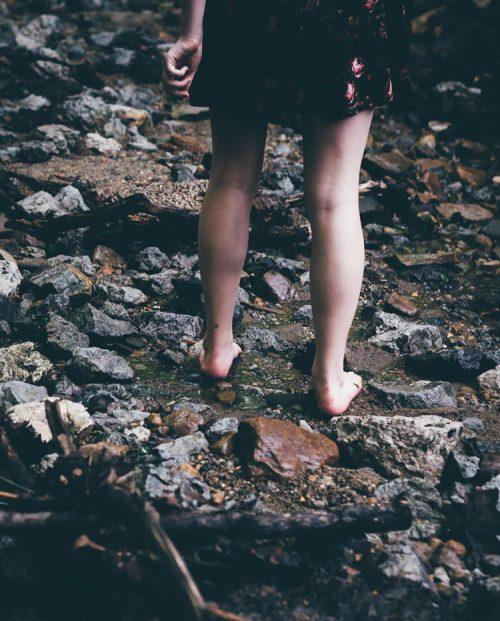 Eine Frau geht barfuß entlang eines steinigen Ufers am Rande eines Sees.
