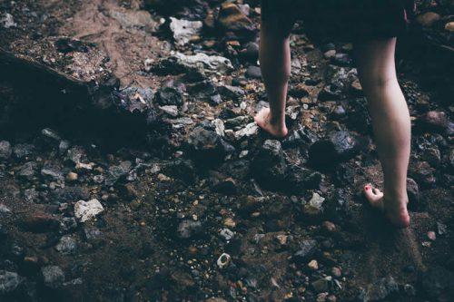 Eine Frau geht barfuß über einen steinigen Waldboden.